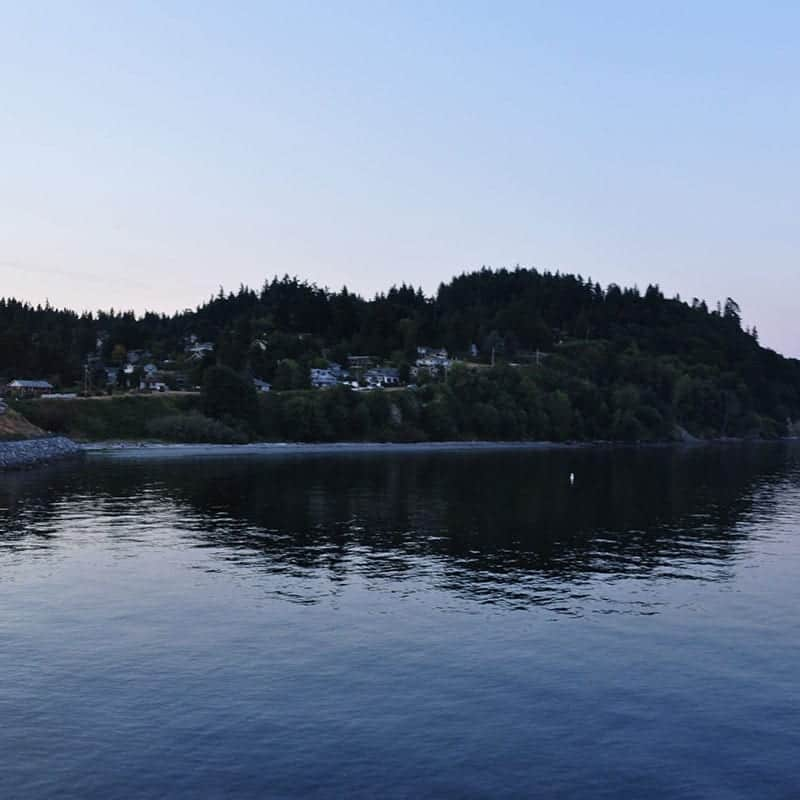 Water front in Kingston Washington. Ocean, homes on waterfront, trees with blue sky.