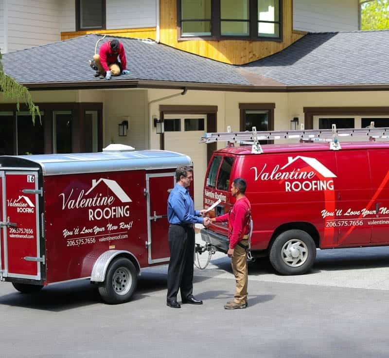 Male roofing customer shaking hands with one of two Valentine Roofing professionals, Valentine Roofing vehicle