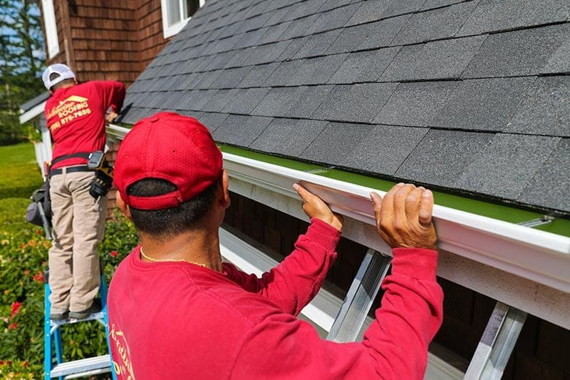 Two Seattle Valentine Roofing gutter contractors installing new gutters.