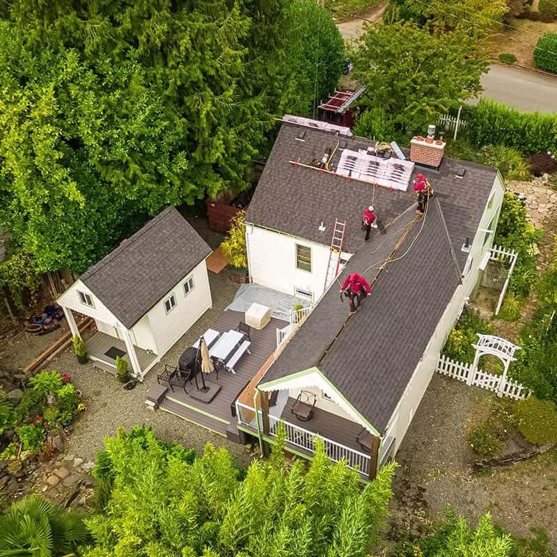 Ariel view of a Seattle roof replacement. Two story home and guest house, Three Valentine Roofers working on top of roof.