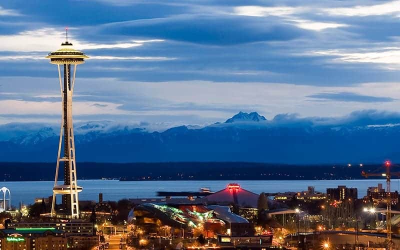 Aerial night view of Seattle waterfront with the Seattle Space Needle other buildings and Cascade Mountain Range as backdrop.