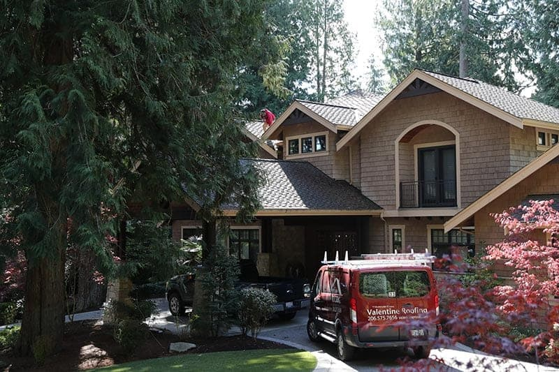 Large evergreen, home with one truck and a Valentine Roofing vehicle. More trees in background