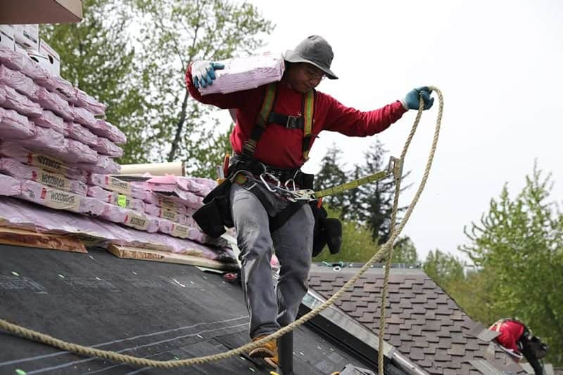 Roofer harnessed to a roof carrying roofing materials with another roofer in the background during a Kent roof repair.