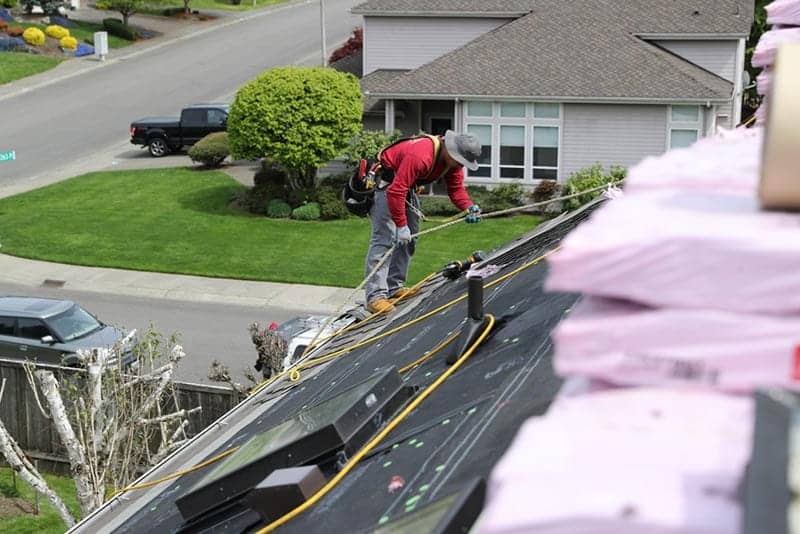 Roofer on top of a home roof replacement project in Puyallup WA