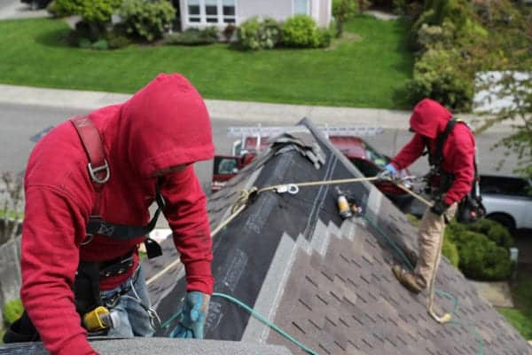 Two Valentine Roofing Contractors performing an Olympia roof replacement.
