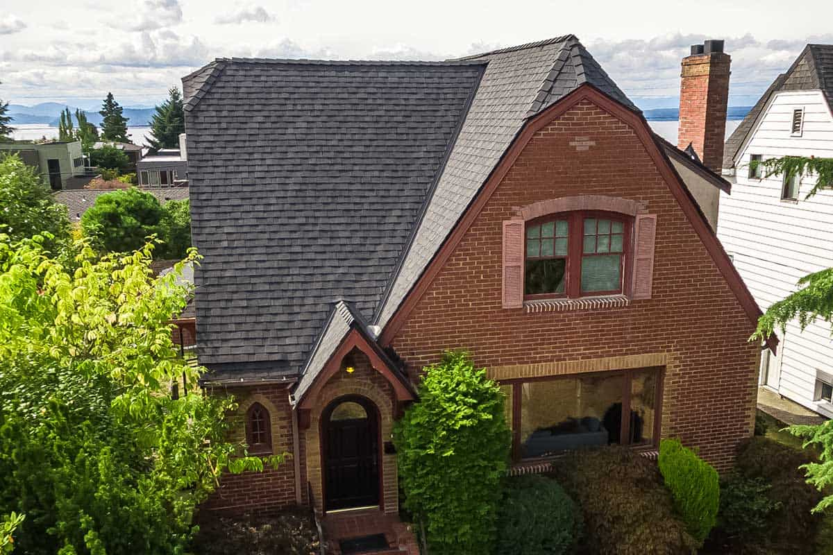 Brick two story home with cleaned roof, other homes, trees and plants and Puget Sound in background.