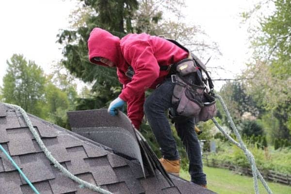 Man on top of a residential roof placing roofing materials while tethered by a safety rope wearing a tool belt with holding roofing tools. Trees and yard with wooden fence in background