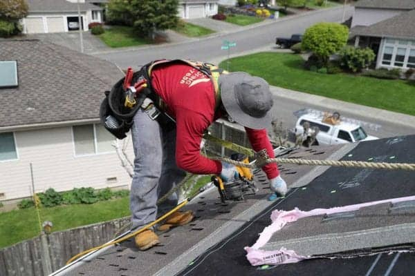 Roofer With Tools On A Rooftop