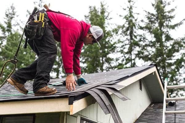 Man gathering roofing shingles on top of a roof wearing tool belt, with roofing tools and a safety rope harness.