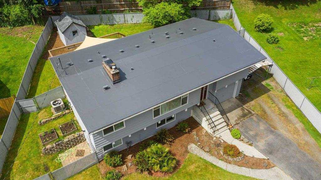 Ariel view of a home with a gray pvc roof.
