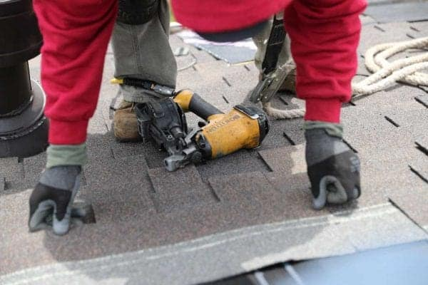 Man on top of a roof installing composite roofing shingles.