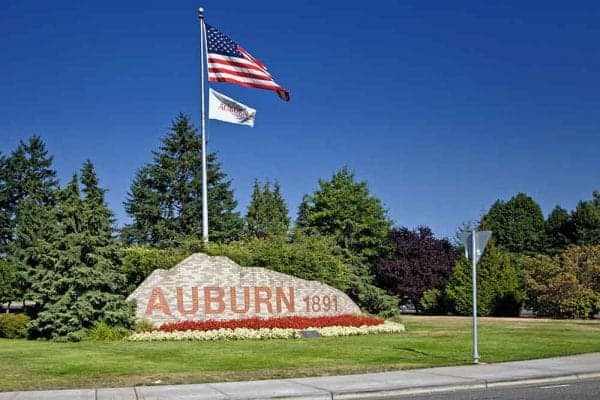 Flag pole with American flag and Auburn Washington flag surrounded by grass and trees.
