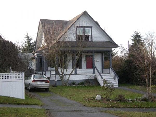 Street view of the front of a traditional two story home. Car in the drive way and stairs to front porch