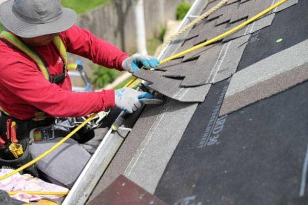 Man wearing a hat, red sweatshirt, jeans, gloves and a well stocked tool belt and saftey harness roped to roof. Installing a composition shingle roof replacement.