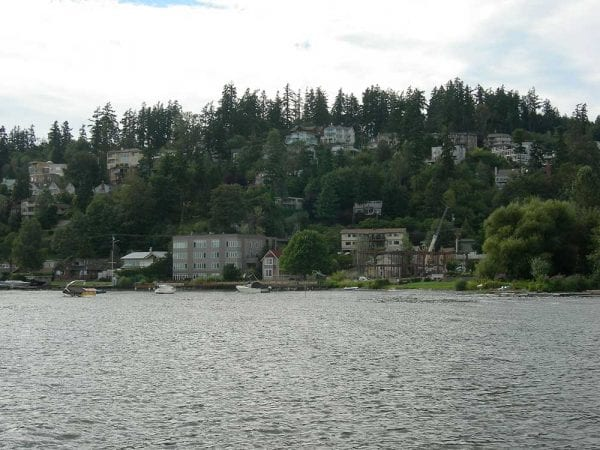 View of Kirkland, WA shoreline from the waters of Lake Washington. Boats, Homes, trees on a hill.