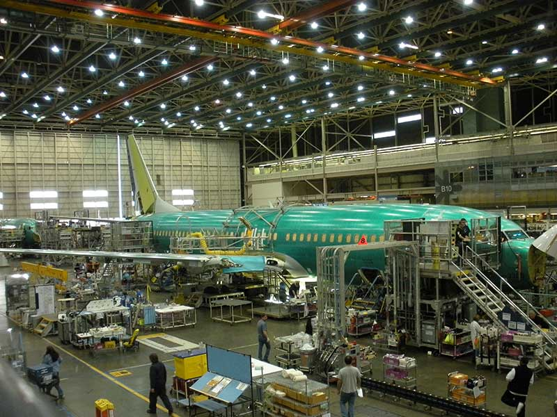 Assembling a Boeing aircraft in hanger with people and equipment surrounding the aircraft