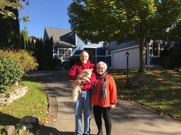 Elderly couple smiling and holding a dog, posing in front of their home. Front yard includes hardscaping, trees with partial view of a neighbors home in background.