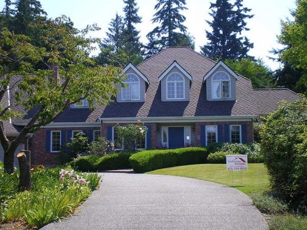 Front view of a large two story home surrounded by a well groomed landscape and evergreen trees