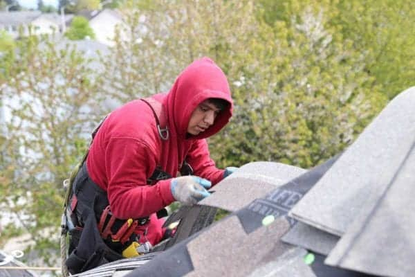 A roofer wearing a red sweatshirt, safety harness, tool belt, inspecting composite roofing shingle