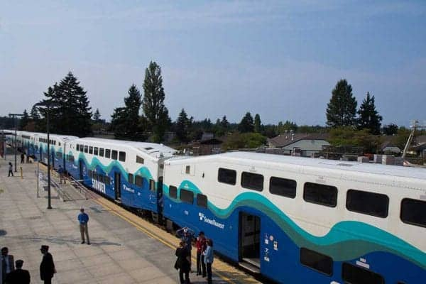 View of a sound transit train boarding passengers. Cement walkway leading to train in foreground with homes and trees in background.