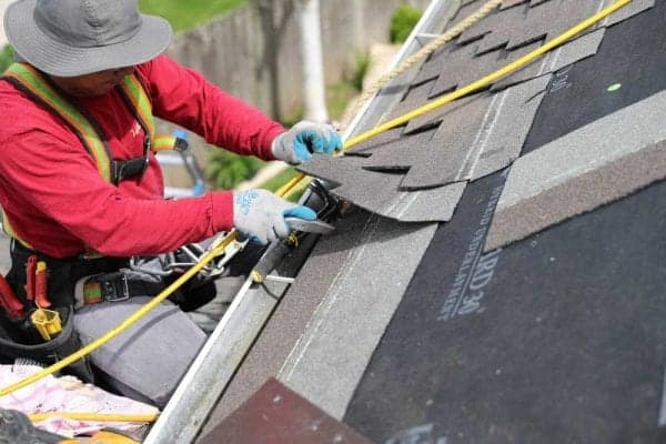 Man installing a new roof wearing jeans, red shirt, safety harness tied to roof and a well equipped tool belt.