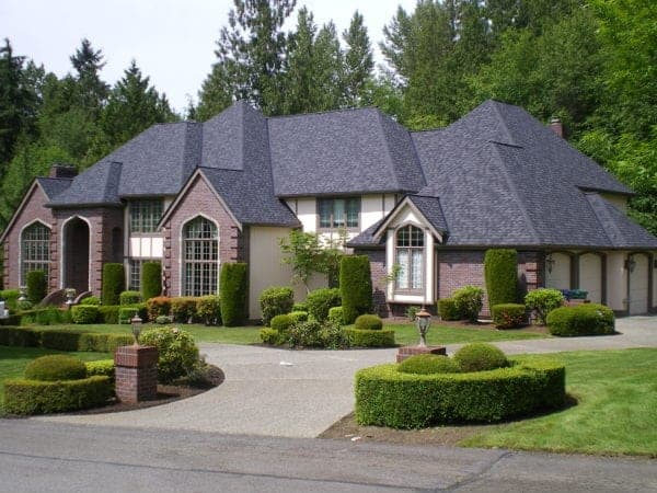 Street view of a very large house with bay windows. There is a circular driveway and meticulously landscaped front lawn.