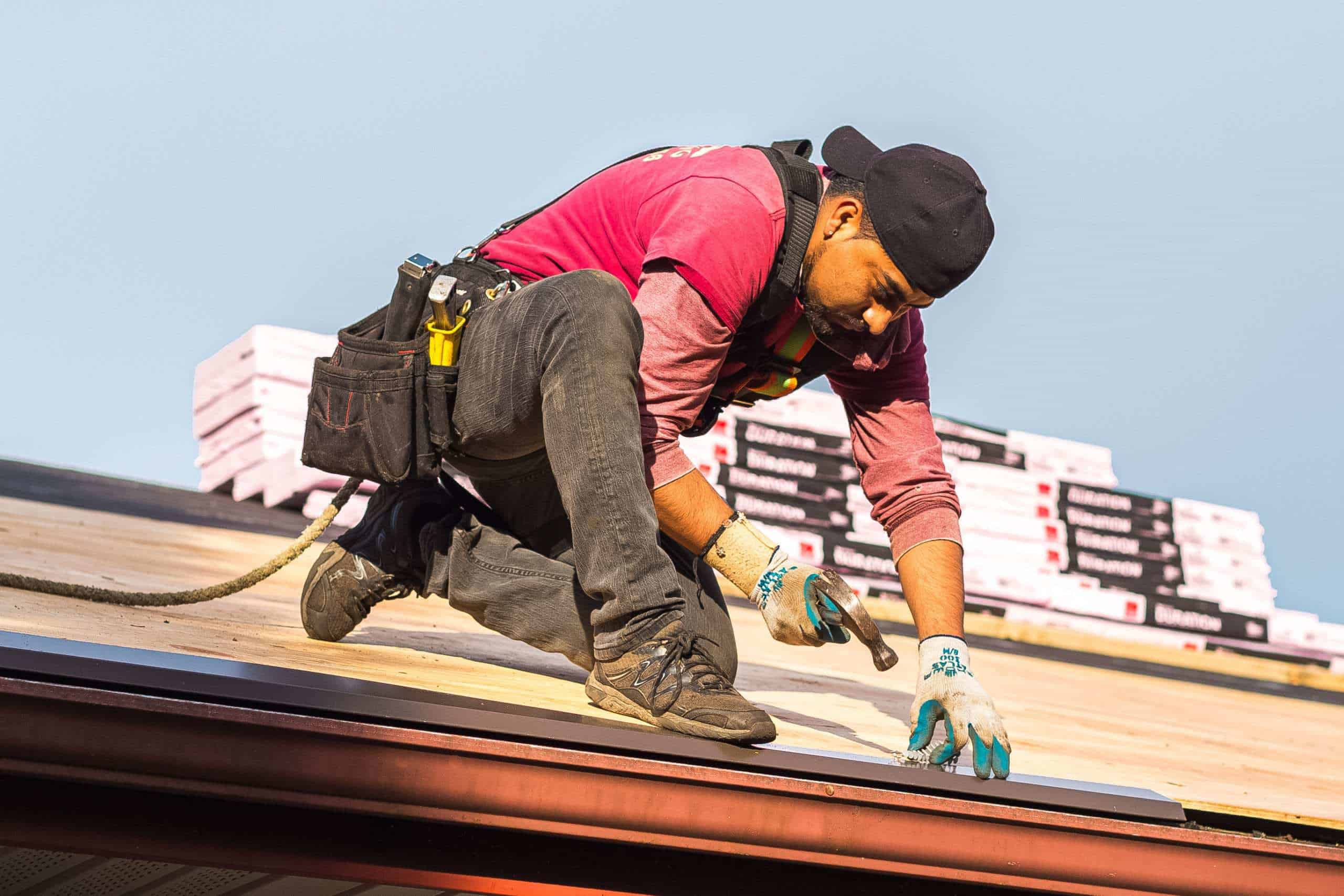 Man hammering a nail in place teathered by safety rope on top of a roof. Roofing materials in background