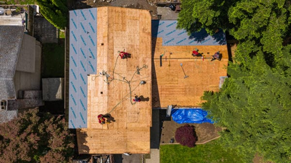Ariel view of a roof during a roof replacement. Surrounded by neighboring home and trees under sunny sky
