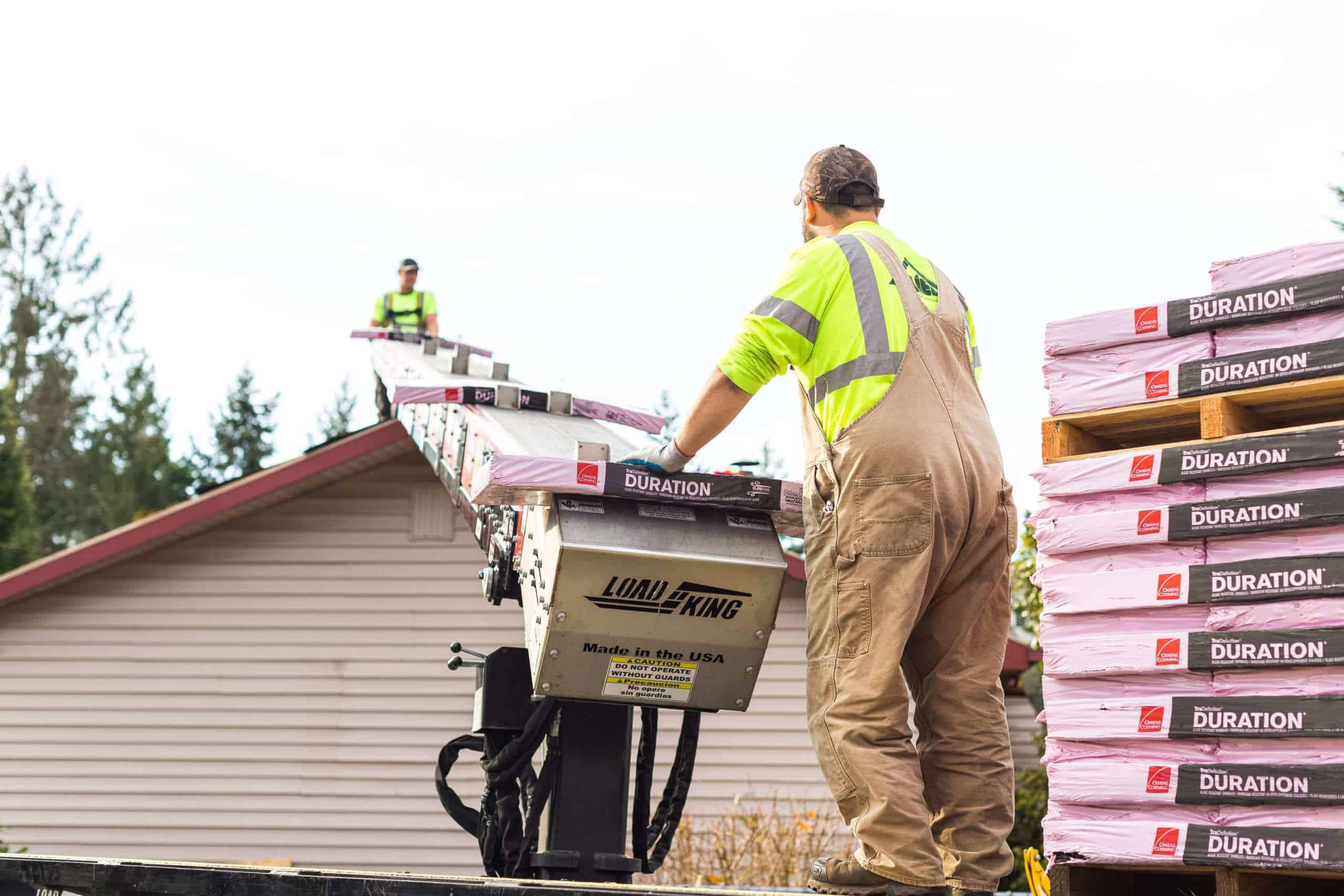Two men using a conveyor belt to move roofing materials to the top of a residential roof