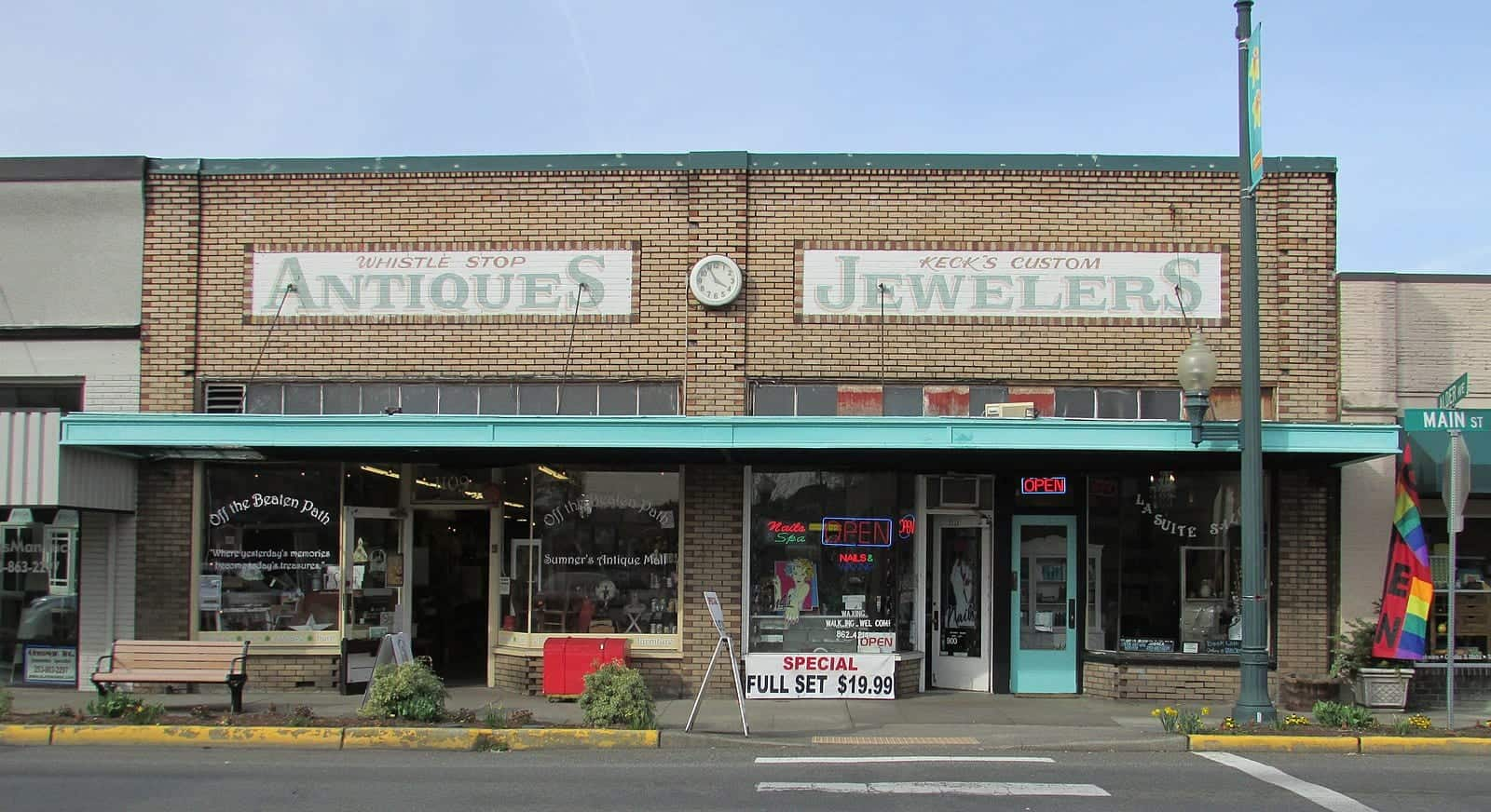 View from the street of a brick building in Sumner, WA containing two adjacent shops. One is an antique shop and a one is a jewelers shop.