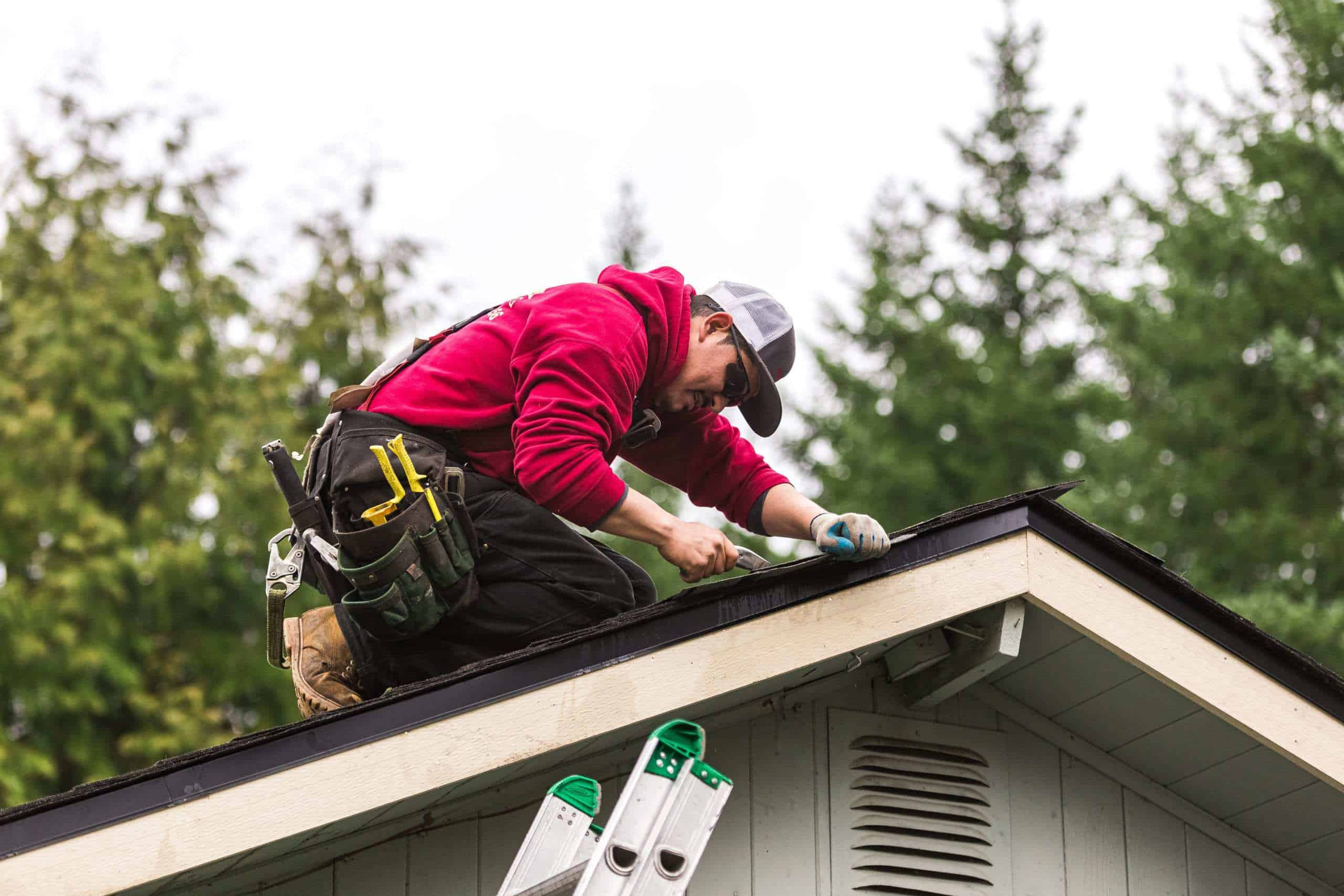 A man kneeling on top of a roof next to the edge. He is using an utility knife to trim the edge of the roof shingles.