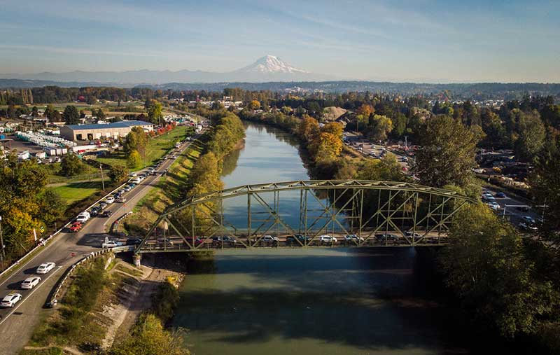 Ariel view of Truss bridge crossing over Puyallup River many cars crossing and Mount Rainier in a distance.