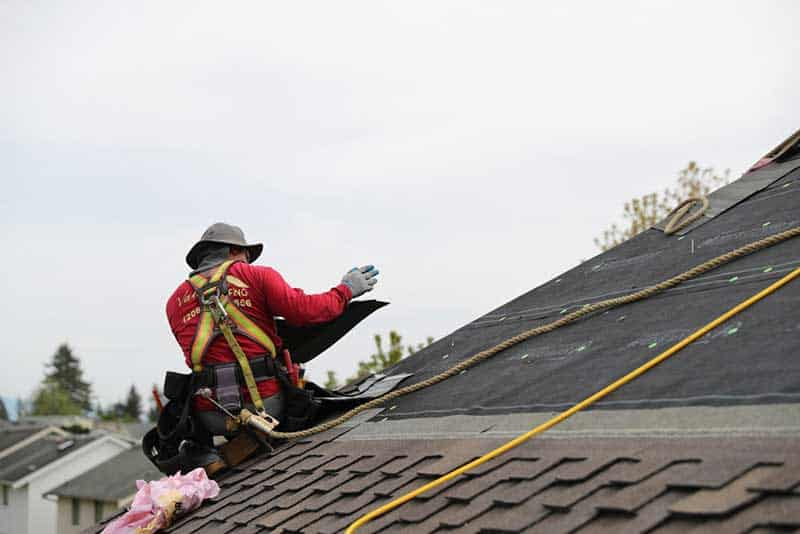 Man on top of roof wearing a roped safety harness while installing roofing shingles.