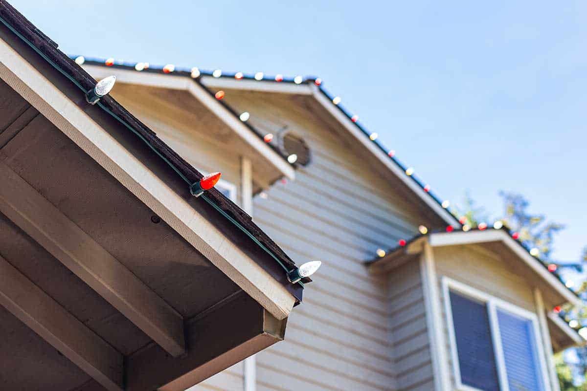 Close-up of various colored Christmas lights hung on house without nails.