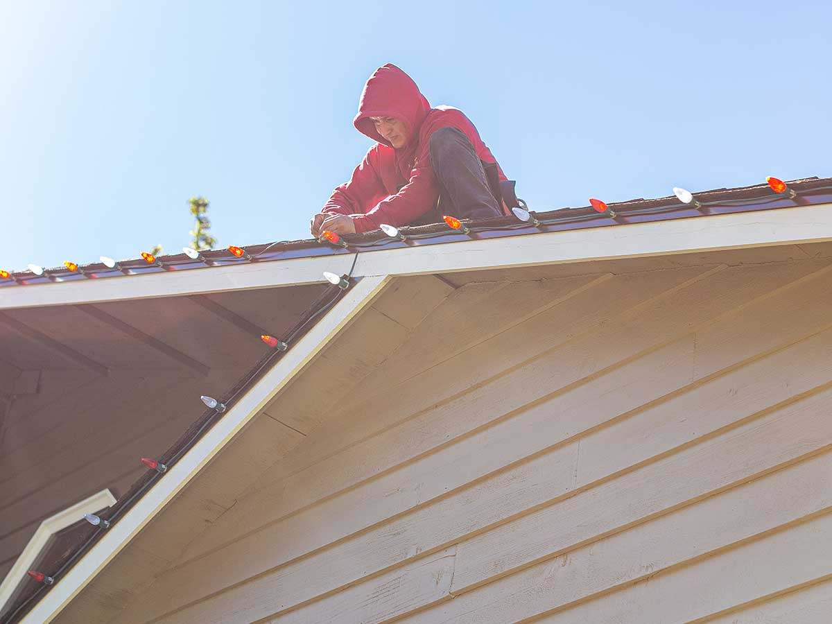 Man with red hoody on roof of house hanging Christmas lights.