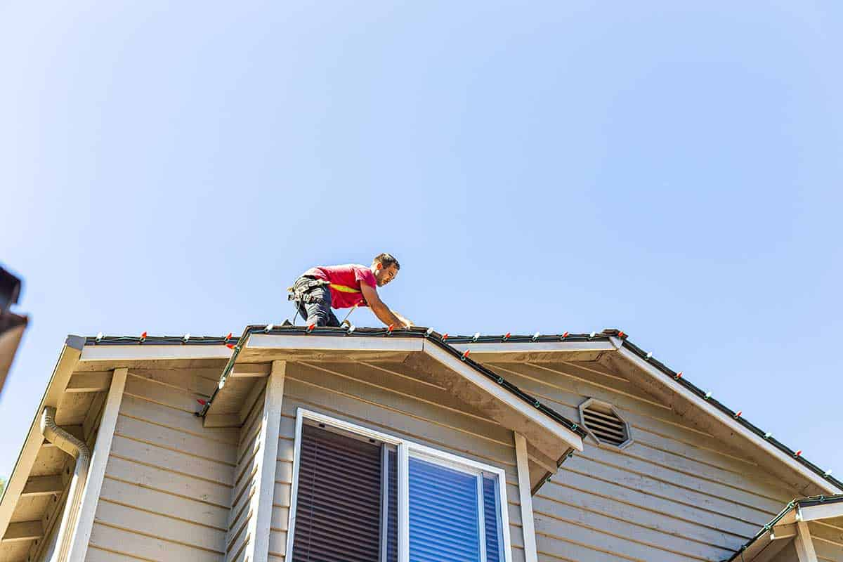 Man harnessed with saftey rope on top of a roof installing holiday lights under a sunny sky.