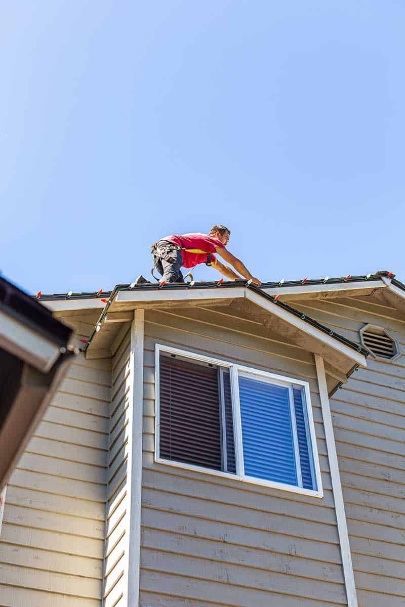 Man on top of a two story home roof installing Christmas lights during daylight hours.