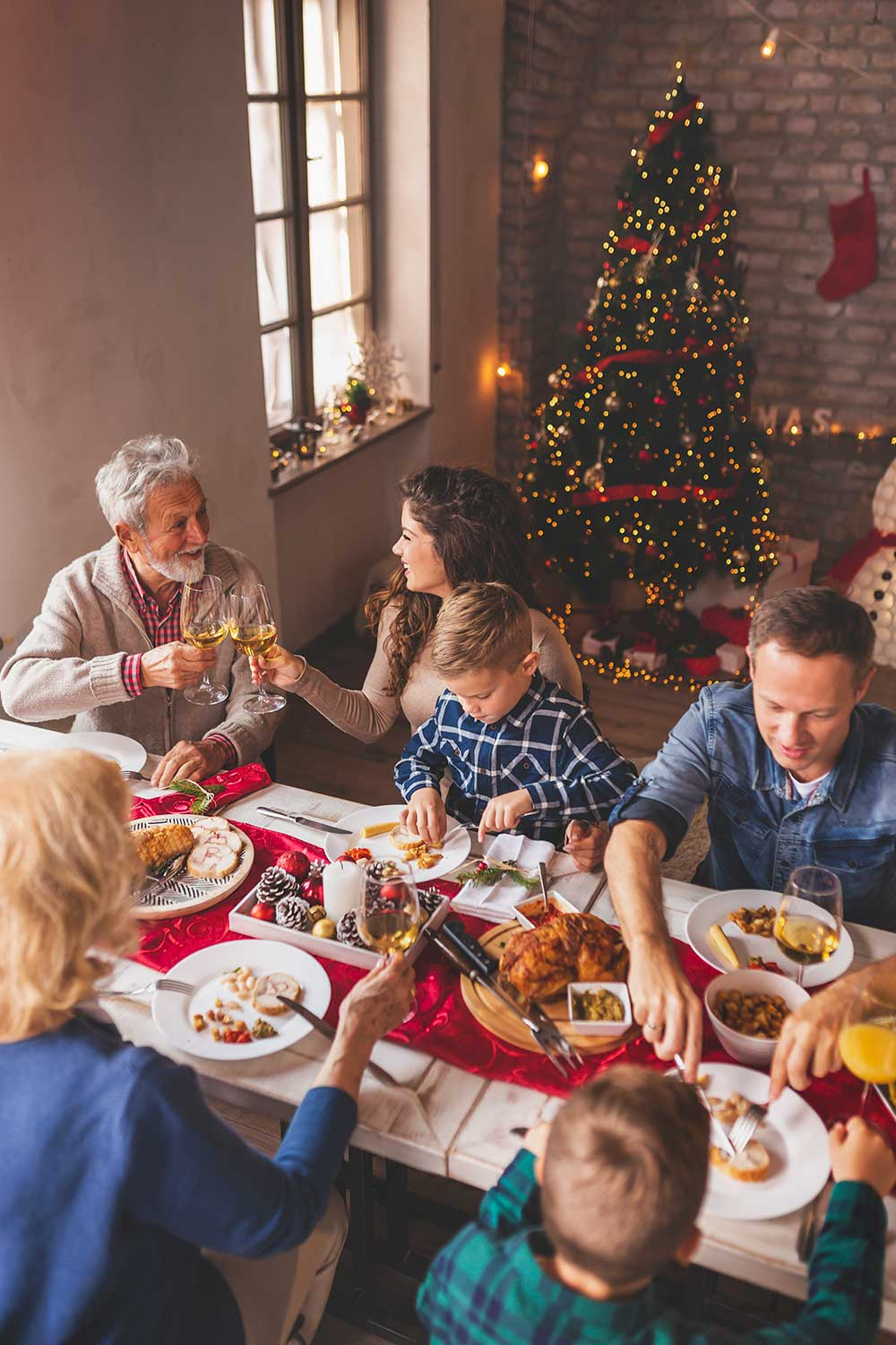 Family enjoying a holiday meal at a table surrounded by Christmas decorations, lights and a Christmas tree.