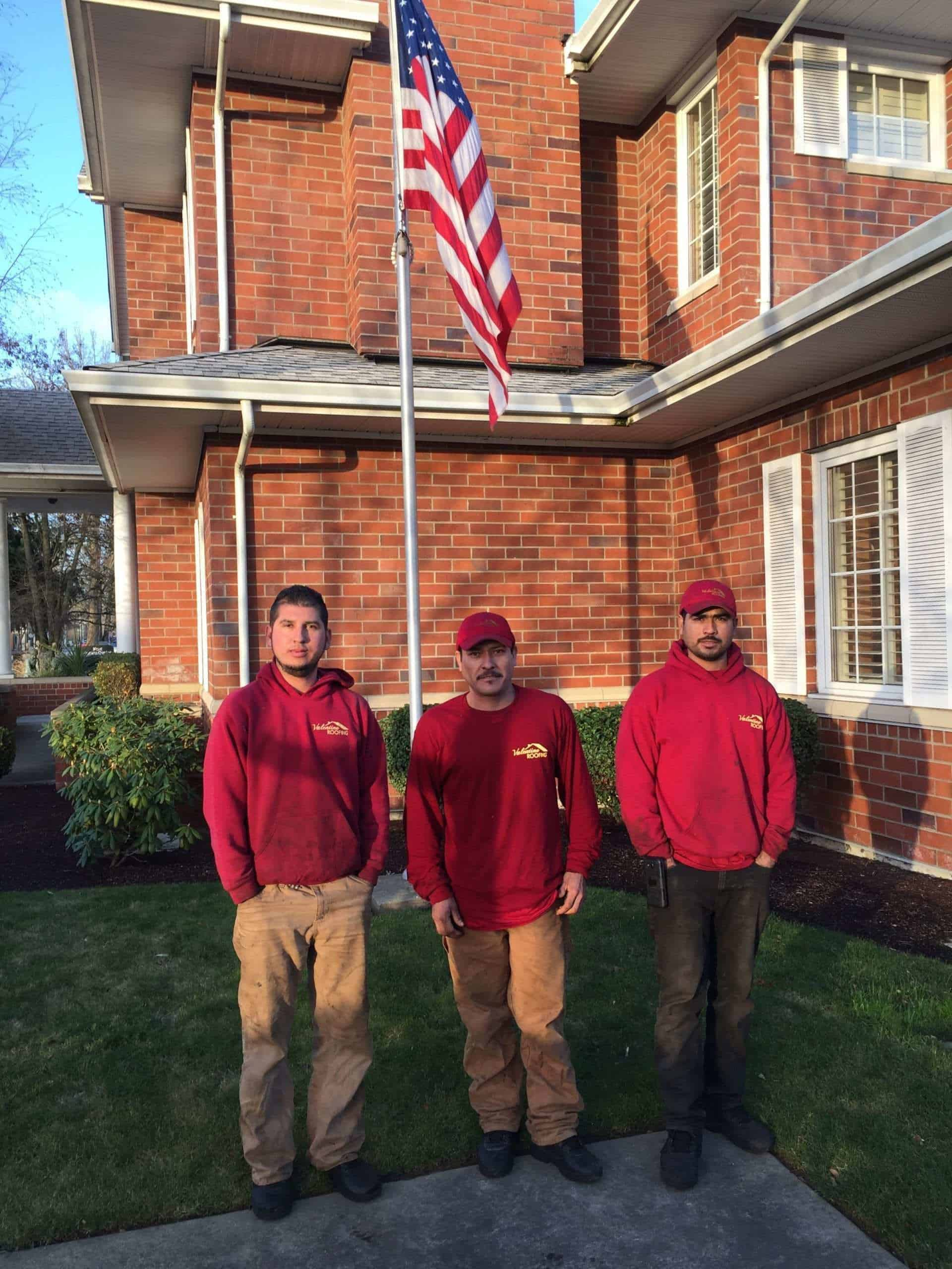 3 male roofers standing under a flag of the United States