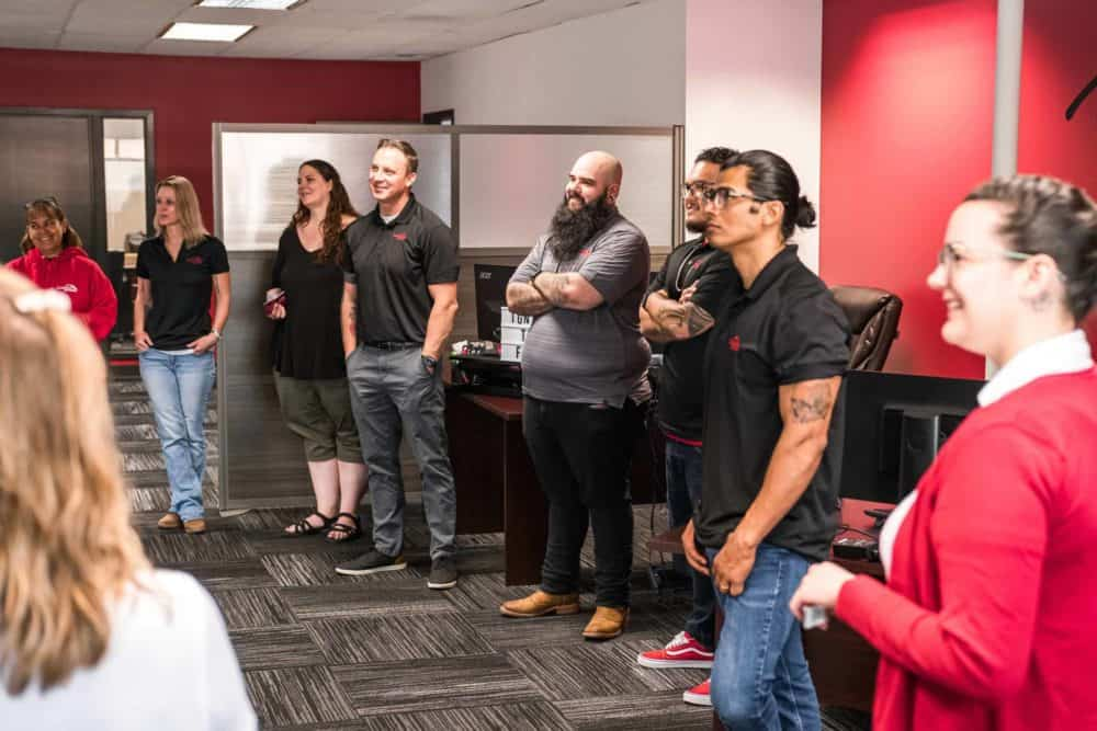 Group of people gathered in a circle for an employee huddle.