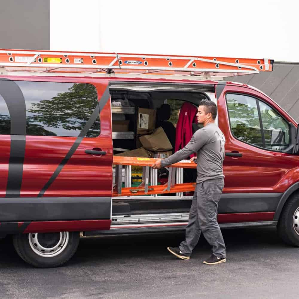 Man unloading ladder from a red van loaded with roofing tools and equipment.