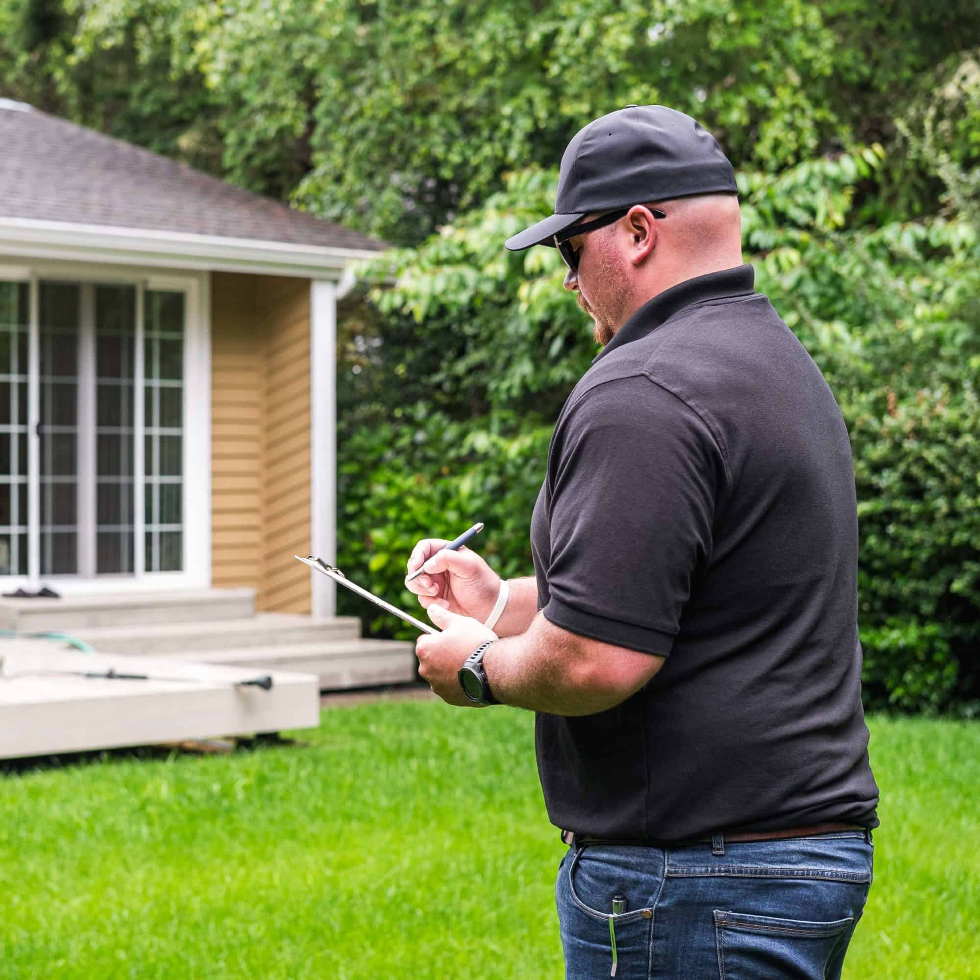 A man standing in front of a partially viewed home holding a clip board while taking notes